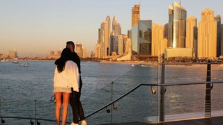 Tourists look at the skyline at sunset, in Dubai, United Arab Emirates