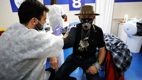 A man receives a vaccination against the coronavirus disease (COVID-19) at a temporary healthcare maintenance organisation (HMO)
