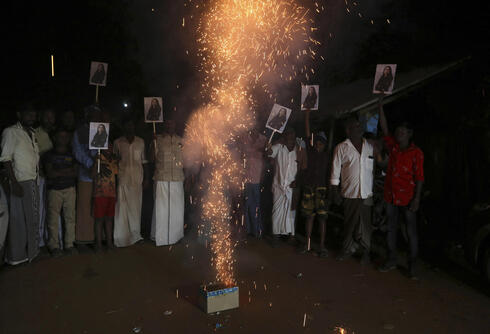 Villagers in Thulasendrapuram burst firecrackers and hold placards featuring U.S. Vice President Kamala Harris after her inauguration, Jan. 20, 2021