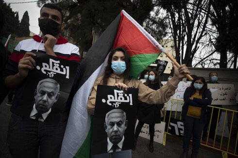 Palestinian protesters hold signs and flags during a demonstration against a visit of Israeli Prime Minister Benjamin Netanyahu to the northern Arab city of Nazareth