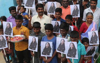 Villagers in Thulasendrapuram, the hometown of Kamala Harris' maternal grandfather, hold photos of the new U.S. vice president, Jan. 20 2021