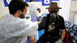 A man is inoculated against coronavirus at a Maccabi HMO vaccination site in the central city of Givatayim