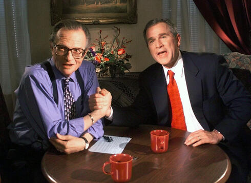 Larry King jokes with Republican presidential candidate George W. Bush after finishing the 'Larry King Live' show, Dec. 1999
