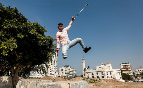 Mohamed Aliwa, a Palestinian youth whose leg was amputated near the knee in 2018 after he was hit by Israeli army fire during protests along the fortified border separating the Gaza Strip from Israel, shows off his parkour skills