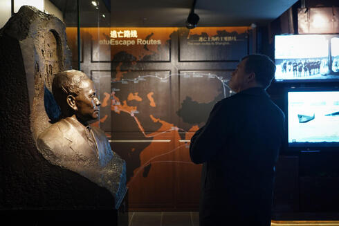 a man standing next to a statue of Ho Feng-Shan (also know as He Fengshan), a Chinese diplomat in Vienna who saved thousands of Jews by giving them Chinese visas between 1938 to 1940, in an exhibition hall at the Shanghai Jewish Refugees Museum