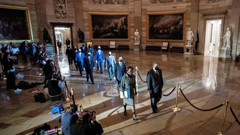 House impeachment managers walk the article of impeachment against former U.S. President Donald Trump through the Rotunda of the U.S. Capitol