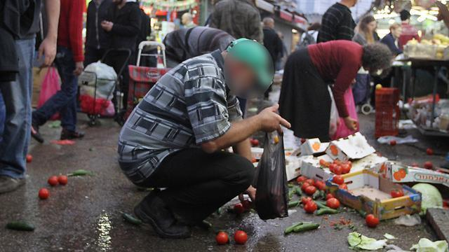 People collecting food from ground in Carmel Market in Tel Aviv before the pandemic