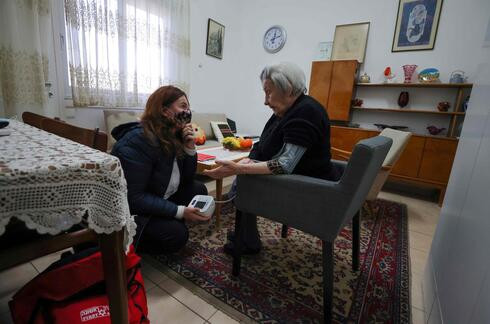Holocaust survivor Miriam Linia receives medical home support from a volunteer on the premises of Israel's Yad Ezer La-Haver foundation, which supports survivors of the Holocaust by providing them food as well as medical and psychological assistance, in the northern port city of Haifa