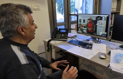 Holocaust survivor Naomie Lichthaus, 86, talks via video call with Shimon Shabag, siting at the call centre of Israel's Yad Ezer La-Haver foundation, which supports survivors of the Holocaust by providing them food as well as medical and psychological assistance, in the northern port city of Haifa