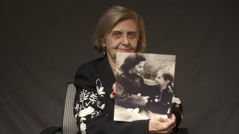 Tova Friedman, an 82-year-old Polish-born Holocaust survivor holding a photograph of herself as a child with her mother, who also survived the Nazi death camp Auschwitz