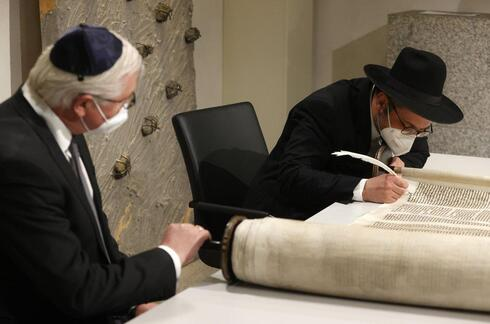 German President Frank-Walter Steinmeier, right, and Rabbi Shaul Nekrich, right, take part in a ceremony at the Reichstag building in Berlin, Germany, Wednesday, Jan. 27, 2021 to complete the historic Sulzbach Torah Scroll from 1792, rediscovered in 2013 and just restored. The ceremony takes place on the International Holocaust Remembrance Day