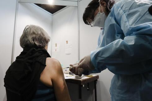 A Holocaust survivor receives an injection of the COVID-19 vaccine at a vaccination center in Vienna, Austria