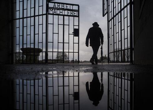 a man walks through the gate of the Sachsenhausen Nazi death camp with the phrase 'Arbeit macht frei' (work sets you free) during International Holocaust Remembrance Day in Oranienburg, about 30 kilometers (18 miles), north of Berlin, Germany