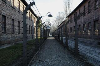 A pathway leading to an observation and security tower between what were electric barbed wire fences inside the former Nazi death camp of Auschwitz I in Oswiecim, Poland