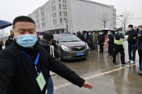 Cars transporting members of the World Health Organization (WHO) team, investigating the origins of the COVID-19 coronavirus, arrive at the closed Huanan Seafood wholesale market in Wuhan, China's central Hubei province