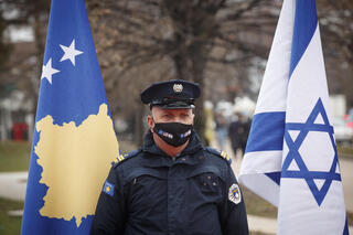 A Kosovar police officer stands next to the flags of Kosovo and Israel