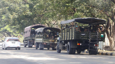 Soldiers sit inside trucks parked on a road in Naypyitaw, Myanmar