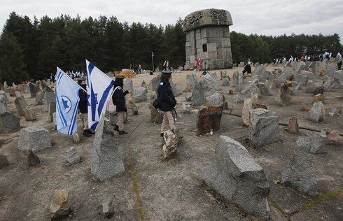Israeli youths with their national flags march by the monument to some 900,000 European Jews killed by the Nazis between 1941 and 1944 at the Treblinka death and labor camp