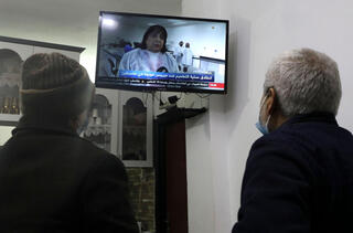 Palestinian men watch a live television broadcast of Palestinian Health Minister Mai al-Kaila announcing the start of vaccination against COVID-19, in the West Bank city of Hebron