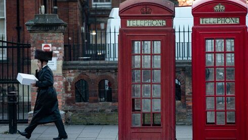 Ultra-Orthodox man walking past London's world-famous red telephone booths