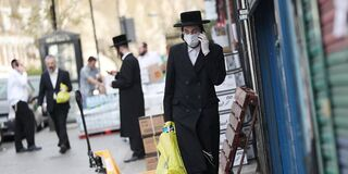 An ultra-Orthodox man dons protective face mask and gloves as he walks in London's Stamford Hill neighborhood during the pandemic