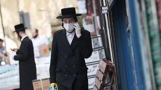 Ultra-Orthodox Jewish man donning protective face mask and gloves walking down London's Stamford Hill neighborhood during COVID-19 pandemic