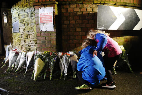Members of the public leave flowers outside the residence of Captain Sir Tom Moore in Marston Moretaine, southern England after his death on Feb. 2, 2021
