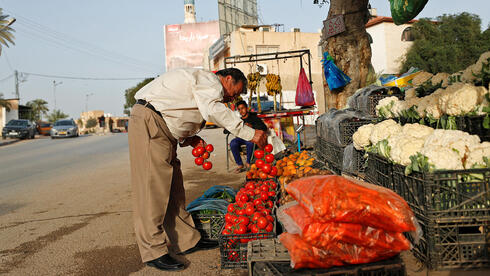Palestinian Businessman Ismail Daiq, who was vaccinated against the coronavirus disease (COVID-19), buys vegetables in Jericho