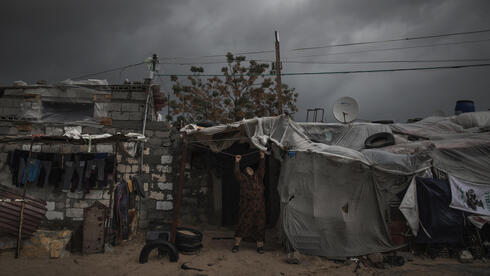 A Gaza woman adjusts a nylon cover on her home last month