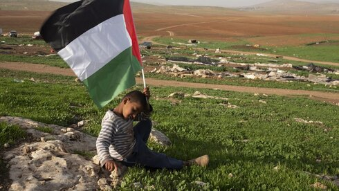 A Palestinian Bedouin boy holds a Palestinian flag after Israeli troops demolished tents and other structures of the Khirbet Humsu hamlet in the Jordan Valley in the West Bank