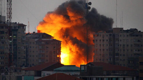 In this file photo taken on August 23, 2014 a ball of fire rises from a building following an Israeli air strike in Gaza City