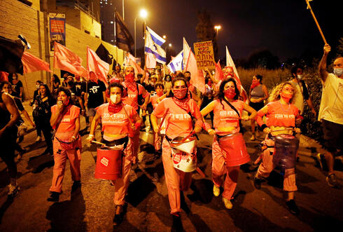 Karin Brauner, Sharon Saguy and Yarden Grosser members of the 'Pink Front' protesters play drums as they march during a weekly anti-Netanyahu demonstration in Jerusalem