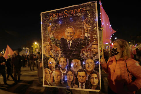 Israeli protesters hold anti-Netanyahu posters during a protest outside his Jerusalem residence, Feb. 6, 2021