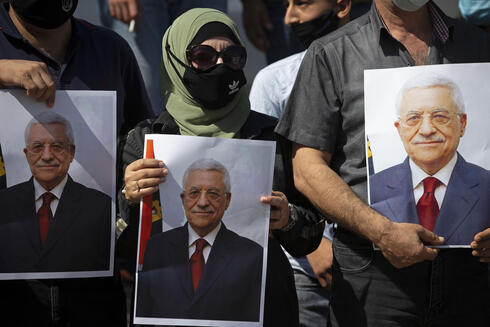 , Palestinians wearing protective face masks amid the coronavirus pandemic, hold pictures of Palestinian President Mahmoud Abbas during a rally to support Abbas