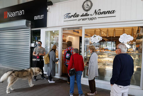 People queue in front of a bakery in Tel Aviv on Sunday following the lifting of a nationwide lockdown