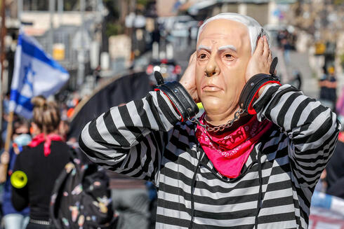 A demonstrator wearing a mask of Benjamin Netanyahu gestures during a protest outside Jerusalem District Court as the prime minister's corruption trial resumes, Feb. 8, 2021