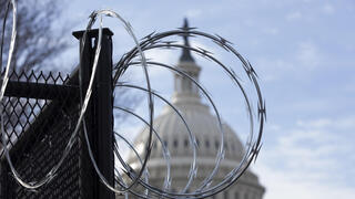 U.S. Capitol seen through barbed wire put in place after the January 6 riots