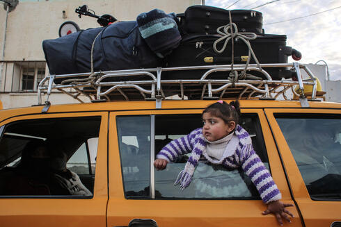 A girl looks on through the window of a vehicle whose top is loaded with suitcases, while waiting at the Rafah border crossing's departure area to travel from the Gaza Strip into Egypt
