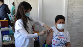 A foreign national receives the COVID-19 vaccine at the new vaccination center in Tel Aviv