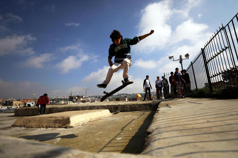 A Palestinian youth jumps with his skateboard on a rooftop as the Dome of the Rock located on the compound known to Muslims as Noble Sanctuary and to Jews as Temple Mount is seen in the background, as Israel partially lifts its third national lockdown to fight the coronavirus disease (COVID-19) crisis, in Jerusalem's Old City