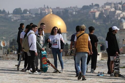 Palestinian youths hold their skateboards while standing on a rooftop, as Israel partially lifts its third national lockdown to fight the coronavirus disease (COVID-19) crisis, in Jerusalem's Old City