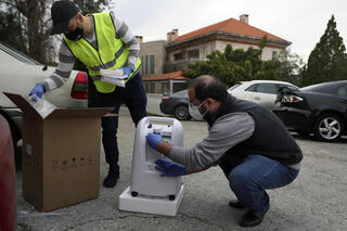 Baytna Baytak members unpack oxygen machine to be donated to an elderly COVID-19 patient in a village north of Beirut, Lebanon