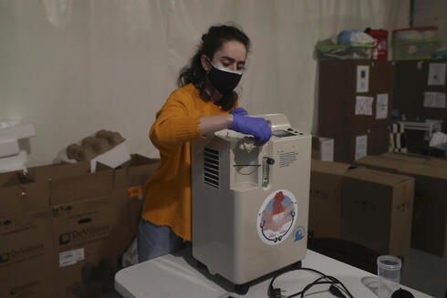Member of Lebanese NGO Baytna Baytak, Gaelle Fenianos, sanitizes an oxygen machine before it is delivered to patients in need, in Beirut, Lebanon