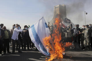 Iranians burn an Israeli flag during a rally in Tehran to mark the 42nd anniversary of the Islamic Revolution, Feb. 10, 2021