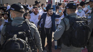 Ultra-Orthodox Jews argue with Israeli border police officers during a protest over the coronavirus lockdown restrictions, in Ashdod