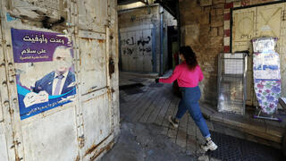 A woman walks past an old campaign poster depicting Ali Salam, the mayor of Nazareth, in the Old City of Nazareth