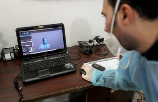 A physiotherapist works on a laptop as he designs 3D transparent face mask for Al-Deeb