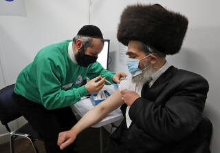 Rabbi Bieberfeld is administered a dose of the AstraZeneca coronavirus vaccine in central London