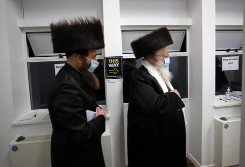 Two men from the Haredi Orthodox Jewish community arrive at an event to encourage vaccine uptake