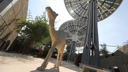People walk at the building of Terra the Sustainability Pavilion at Expo 2020 Dubai site